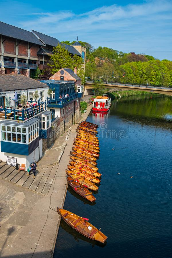 Line of moored rowing boats on the banks of River Wear near a boat club in Durham, United Kingdom on a beautiful spring afternoon. Durham, United Kingdom - April royalty free stock photography