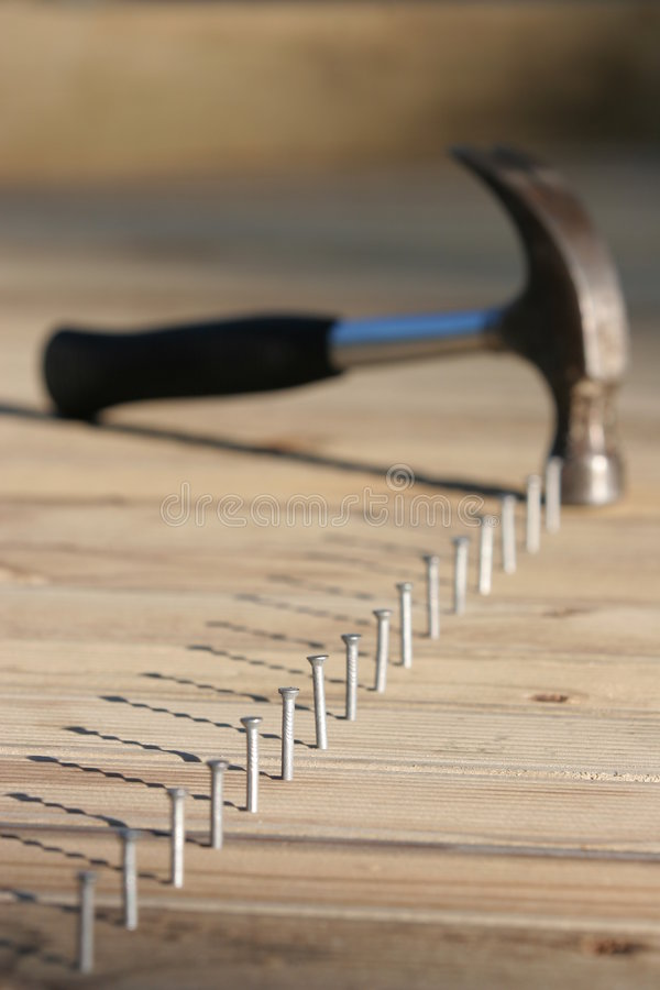 Line of nails and hammer. Line of nails in timber decking, only one nail in focus, very shallow depth of field. Hammer has driven last nail fully down royalty free stock photos