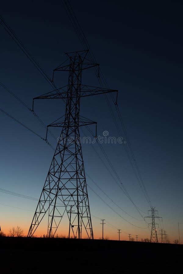 Line of power line towers around sunrise stock image