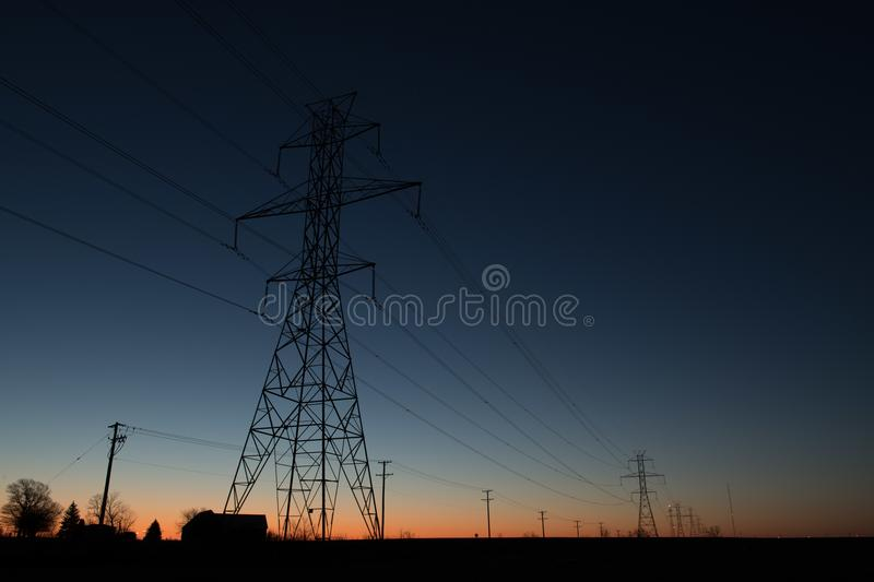 Line of power line towers around sunrise royalty free stock images