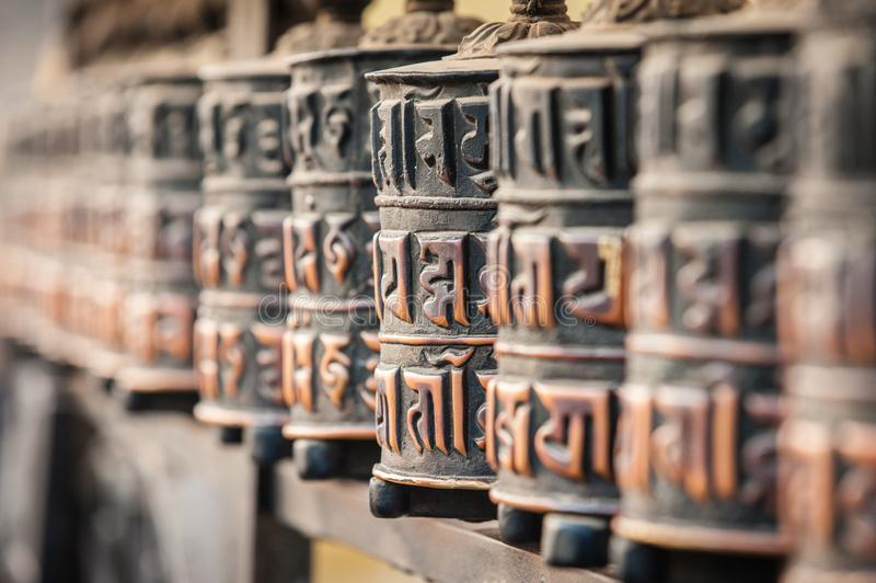 Line of prayer wheels in a village on the Annapurna circuit trail. Buddhist Prayer Mills. Himalayas. Nepal. Asia. Detail. royalty free stock photo
