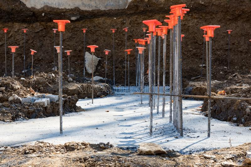 Line of rebar steel rods in poured concrete footings stock image