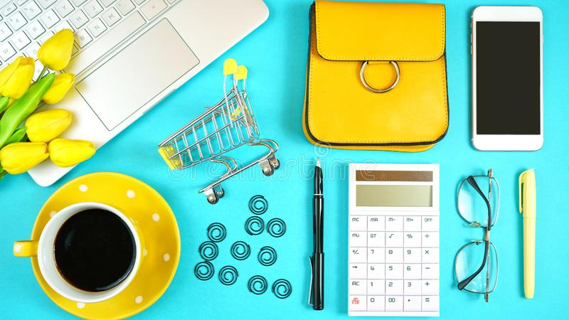 On-line shopping concept flatlay with shopping cart and accessories. Online shopping concept with laptop, shopping cart, smart phone, calculator, coffee and stock photo