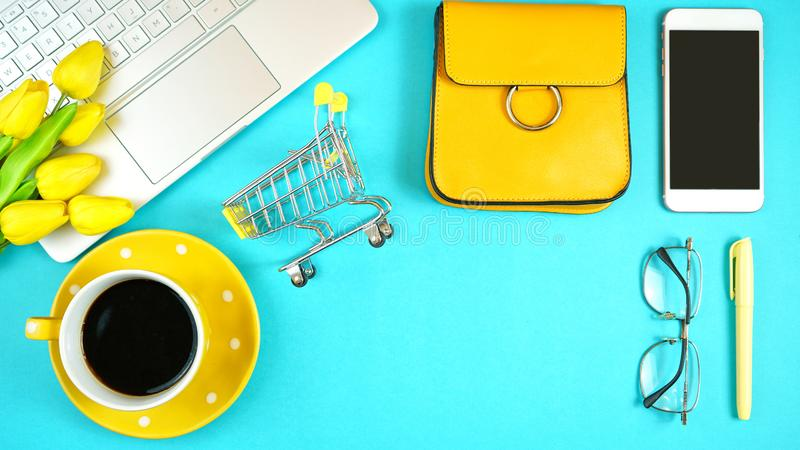On-line shopping concept flatlay with shopping cart and accessories. Online shopping concept with laptop, shopping cart, smart phone, calculator, coffee and royalty free stock image