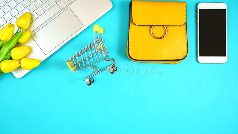 On-line shopping concept flatlay with shopping cart and accessories. Online shopping concept with laptop, shopping cart, smart phone, calculator, coffee and royalty free stock images