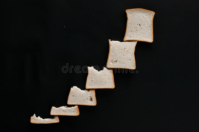 A line of slices of bread which are getting bigger and bigger, on a black background. Shot from above royalty free stock photography