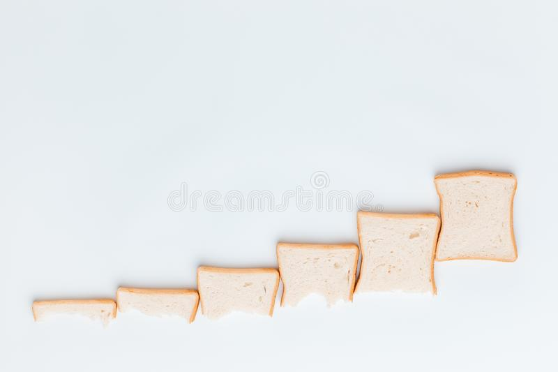 A line of slices of bread which are getting bigger and bigger, on a white background. Shot from above royalty free stock images