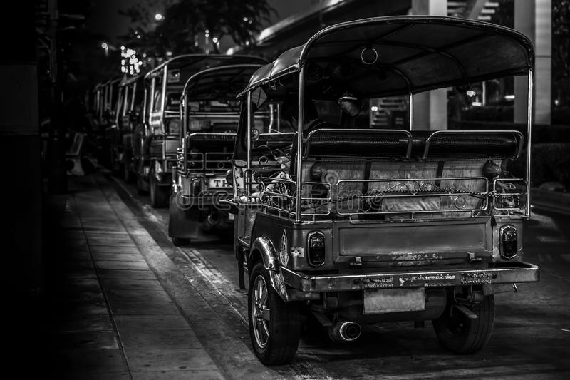 A line of Tuk Tuk waiting for the passengers on a street in Bangk royalty free stock image