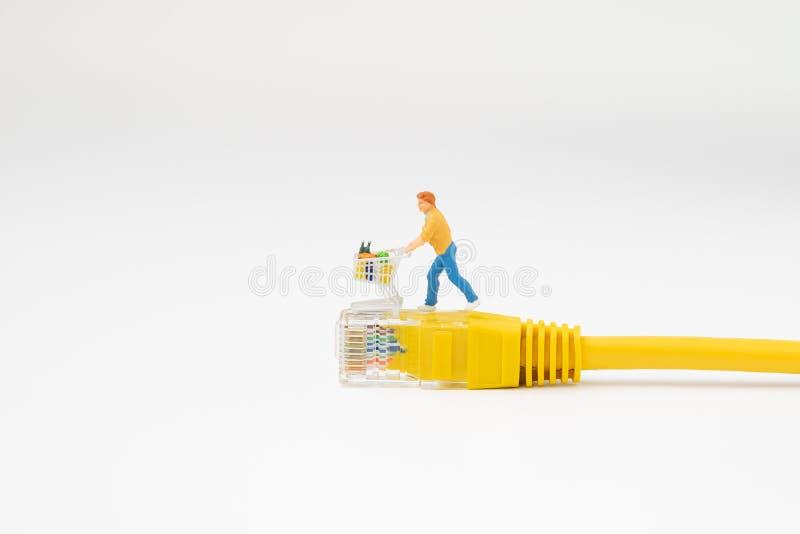 On-line-- und E-Commerce-Einkaufskonzept, Miniaturleutefigürchen-Laufkatzeneinkaufswagen mit vollem Lebensmittelgeschäft in LAN-I stockbild