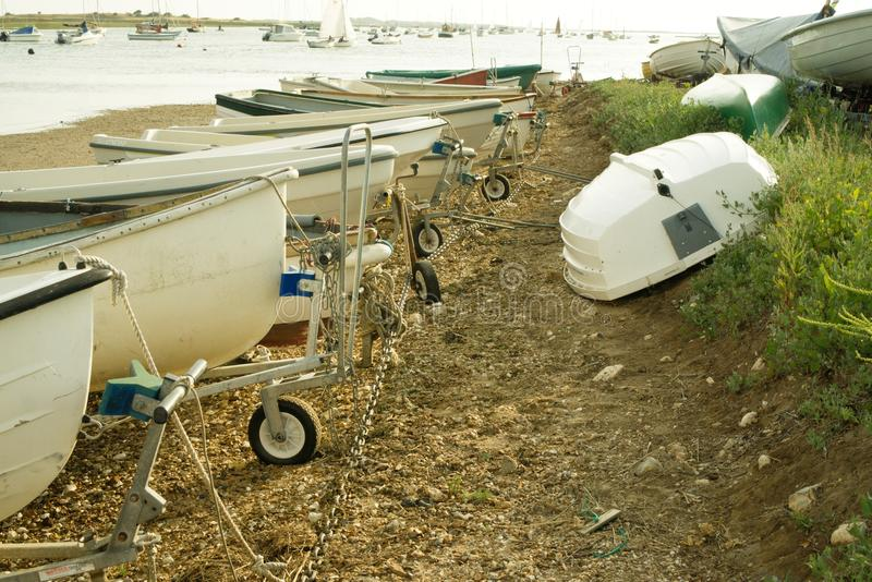 Dinghy's in Brancaster Staithe harbour. Dinghy`s lined up and plenty of activity in the background in this busy summer harbour at Brancaster Staithe royalty free stock photos
