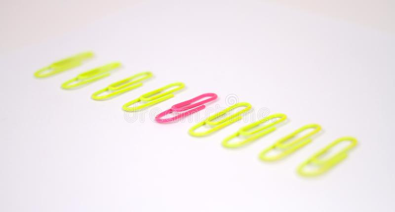 Line of yellow paperclips and a pink odd one out royalty free stock photos