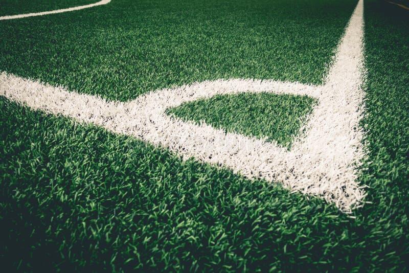 Linea bianca di scossa d'angolo sull'erba del manufatto sulla terra di calcio fotografia stock libera da diritti