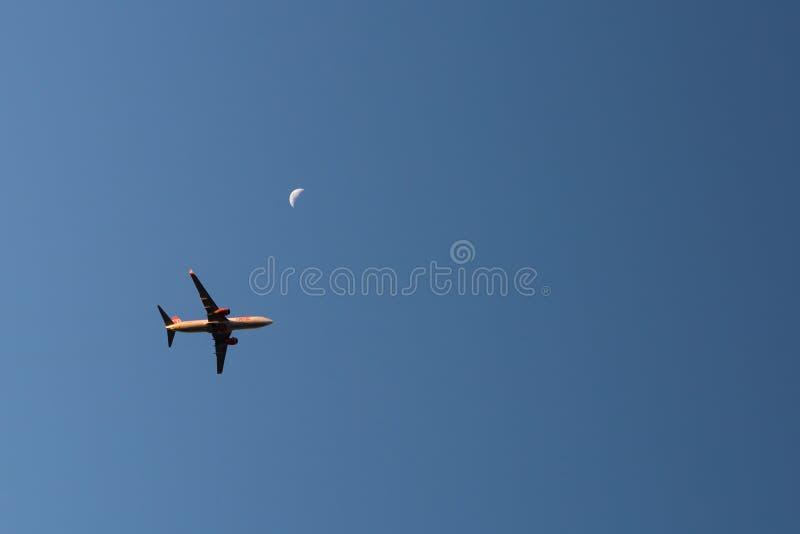 Linea commerciale aeroplano di volo con la luna di aumento nei precedenti durante il tramonto fotografie stock libere da diritti