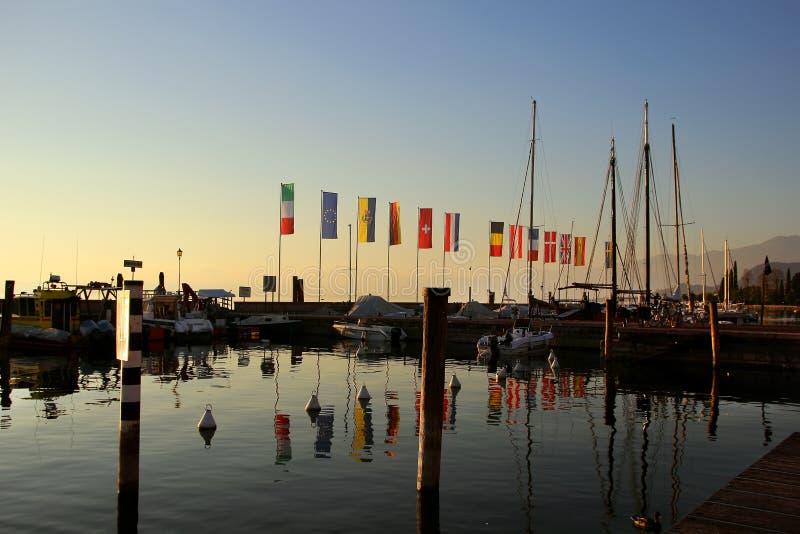 Linea costiera con le aste della bandiera e le barche fotografie stock
