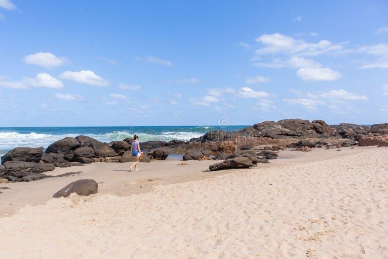 Linea costiera di camminata dell'oceano della spiaggia della ragazza fotografie stock libere da diritti