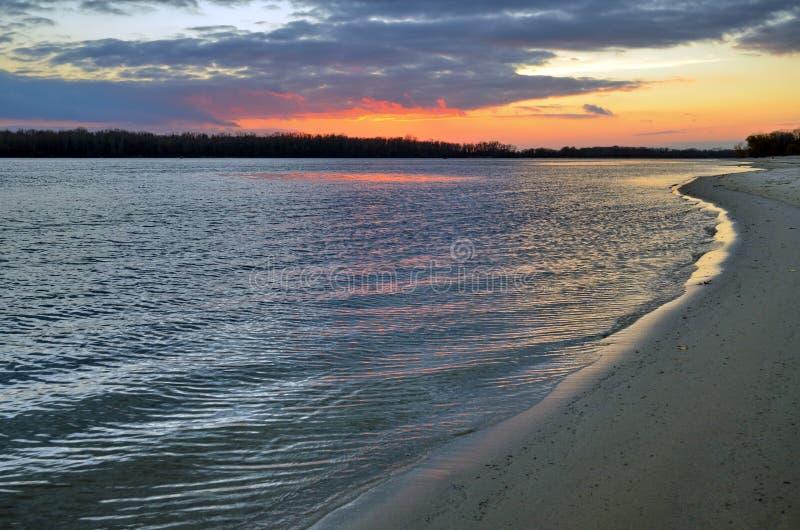 Linea costiera sulla riva sabbiosa di grande fiume al tramonto immagini stock