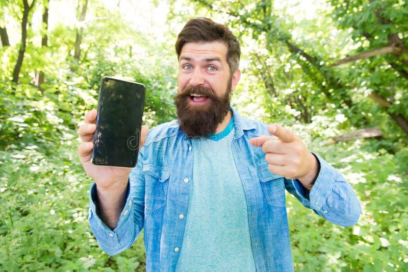 In linea dappertutto uomo barbuto felice sul telefono Pantaloni a vita bassa maturi con la barba che indicano dito perso nell'uom fotografia stock