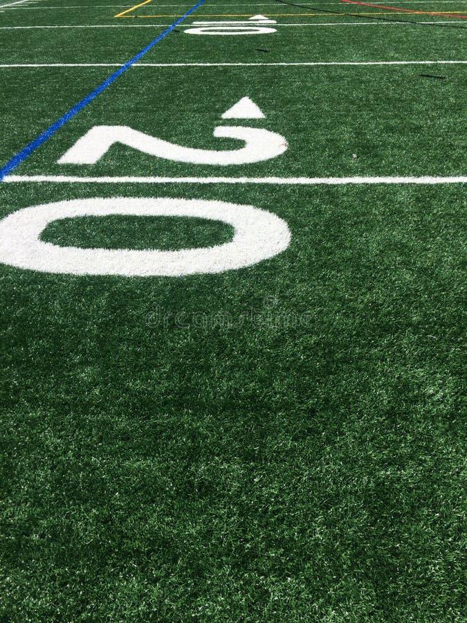 Linea delle yard del campo di football americano 20 del tappeto erboso Campo di football americano del tappeto erboso fotografie stock libere da diritti