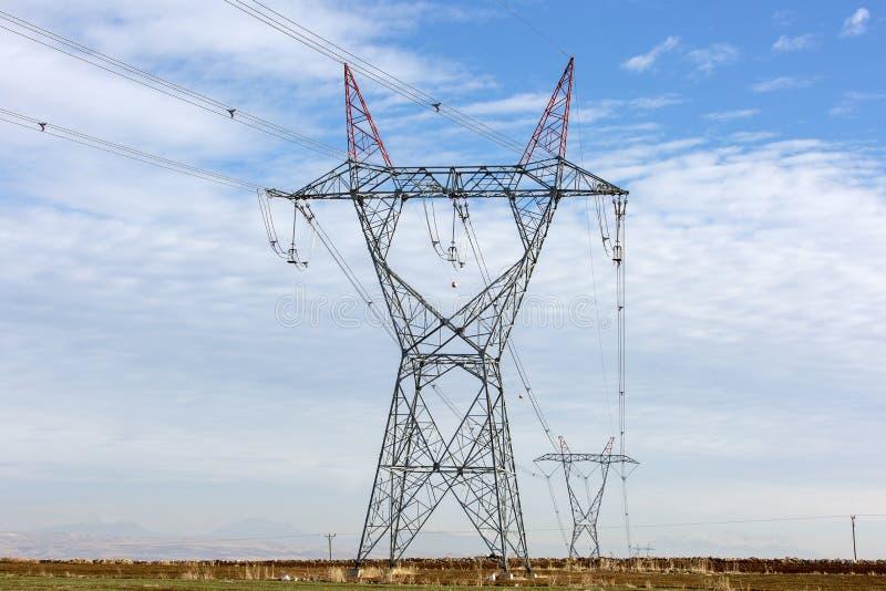 Linea di alta tensione di industria di elettricità torri fotografia stock libera da diritti