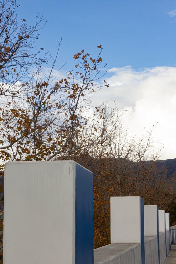 Linea di colonne concrete sulla parete con le foglie di caduta dello sycacore fotografie stock libere da diritti