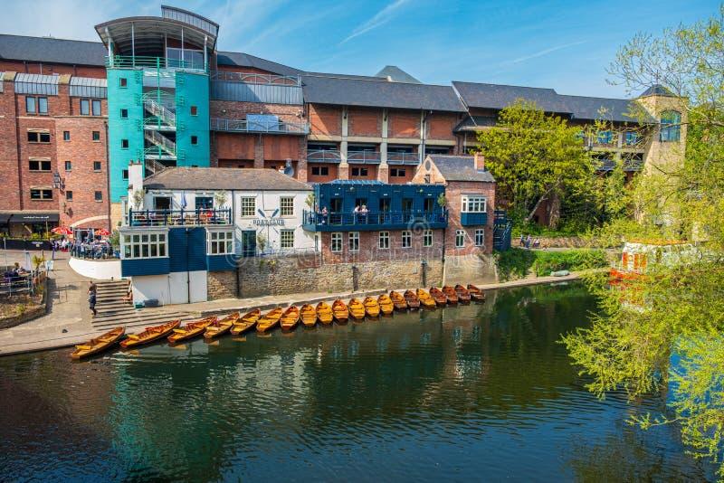 Linea di imbarcazioni a remi attraccate sulle banche di usura del fiume vicino ad un club della barca a Durham, Regno Unito su un immagine stock libera da diritti