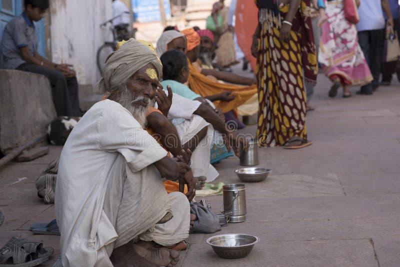 Linea di mendicanti che si siedono fuori di un tempio in India fotografia stock