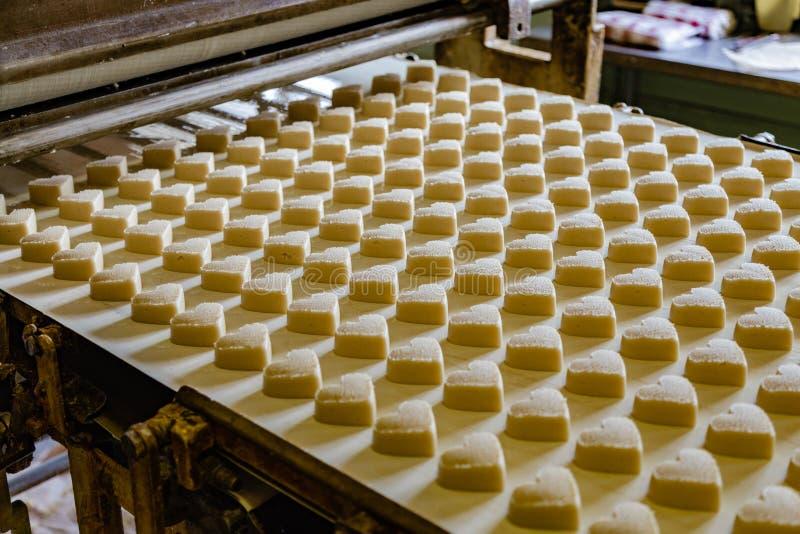 Linea di produzione di cottura Biscotti crudi crudi nella forma di cuori dopo la formazione andare al forno dal trasportatore fotografia stock