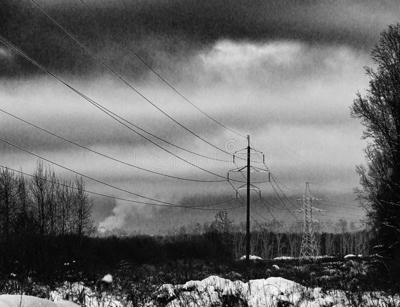Linea elettrica ad alta tensione della trasmissione nell'orario invernale di entroterra fotografia stock