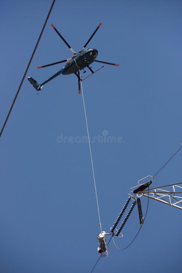 Linea elettrica ad alta tensione pericolosa lavoro da un elicottero fotografie stock libere da diritti