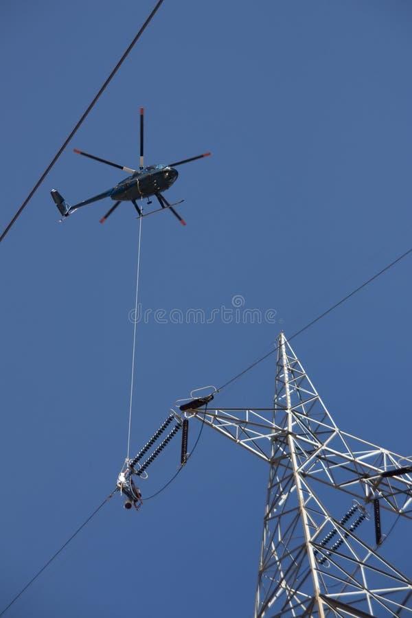 Linea elettrica ad alta tensione pericolosa lavoro da un elicottero fotografia stock libera da diritti