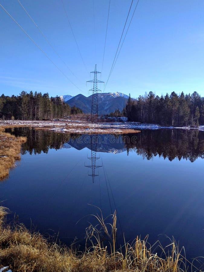 Linea elettrica di Taiga e lago della foresta immagine stock