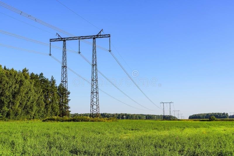 Linea elettrica trasmissione di energia elettrica sulle costruzioni metalliche ad alta tensione fotografia stock libera da diritti