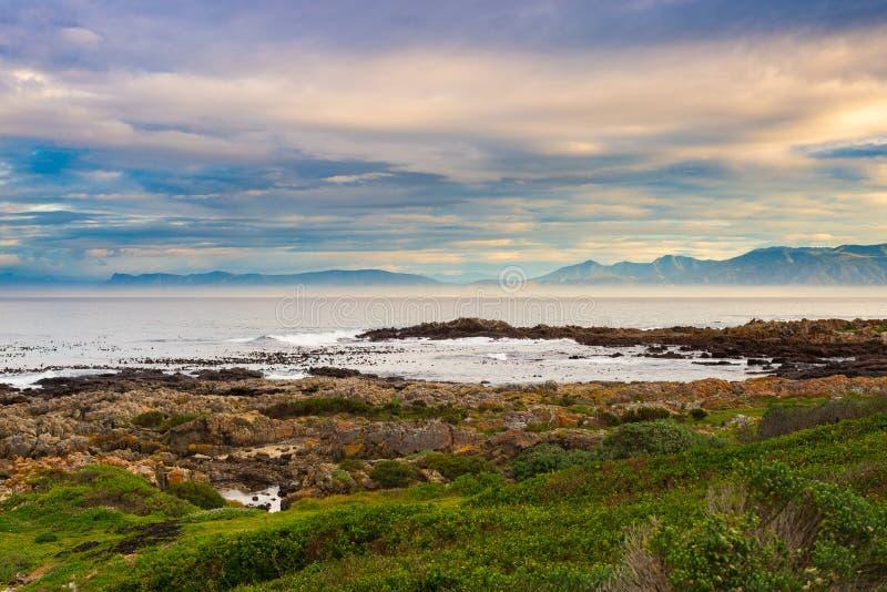 Linea rocciosa della costa sull'oceano a De Kelders, Sudafrica, famoso per la sorveglianza della balena Cielo nuvoloso e drammati fotografie stock libere da diritti
