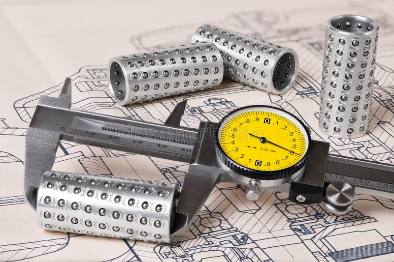 Linear ball bearings measurement. Caliper gauge. Technical drafting. Measuring of steel rollers and plan. Vernier tool with round yellow dial. Group of metal royalty free stock photo