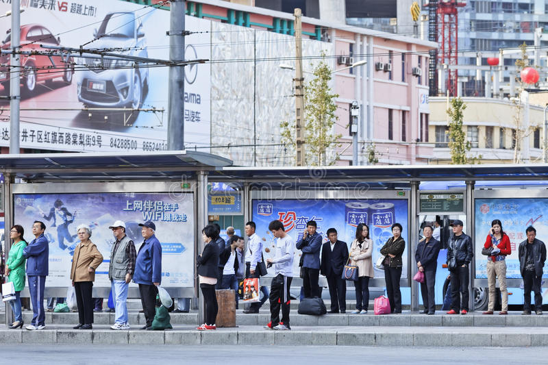 Lined up people at bus staion, Dalian, China. DALIAN-CHINA-OCT. 14, 2012. Station with advertising on Oct 14, 2012 in Dalian. China has 50,000 outdoor stock image