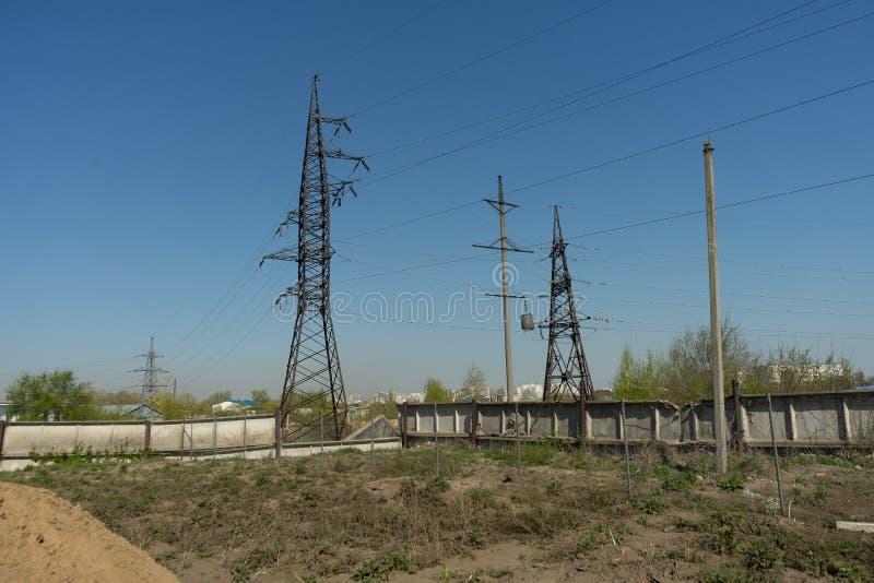 Linee ad alta tensione e piloni di potere nella zona industriale un giorno soleggiato con un chiaro cielo blu immagini stock libere da diritti