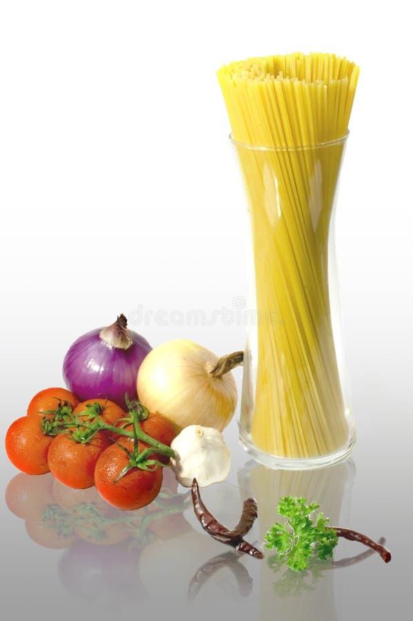 Linee di spaghetti in una bottiglia di vetro alta con le verdure fotografia stock
