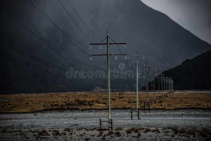Linee e pali di trasmissione che attraversano la pianura alluvionale fotografia stock libera da diritti