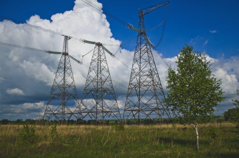 Linee elettriche ad alta tensione sul campo fotografia stock libera da diritti