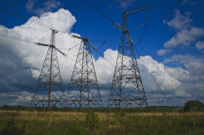 Linee elettriche ad alta tensione sul campo fotografie stock libere da diritti