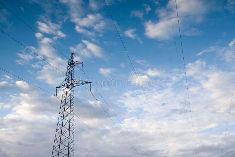 Linee elettriche della centrale elettrica, sulla protezione del cielo blu immagini stock libere da diritti