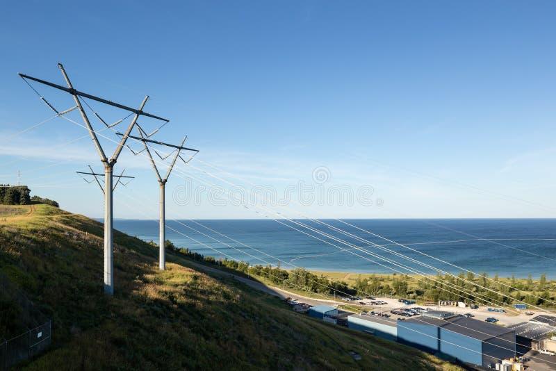 Linee elettriche di potere dall'idro pianta elettrica sull'acqua di riunione della collina immagine stock