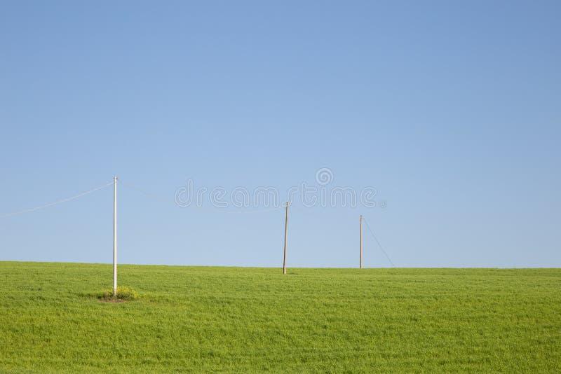 Linee elettriche su un prato verde sotto un cielo blu fotografie stock libere da diritti