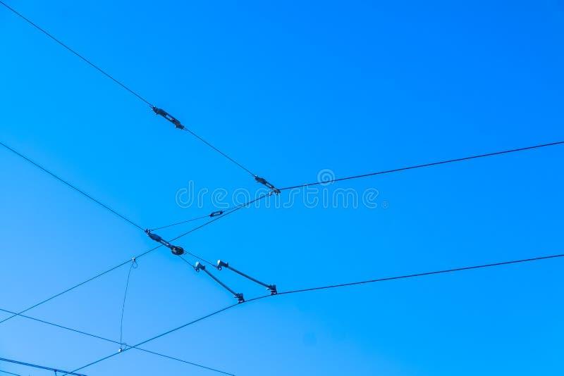 Linee sopraelevate della ferrovia contro il chiaro filo di contatto del cielo blu immagine stock libera da diritti