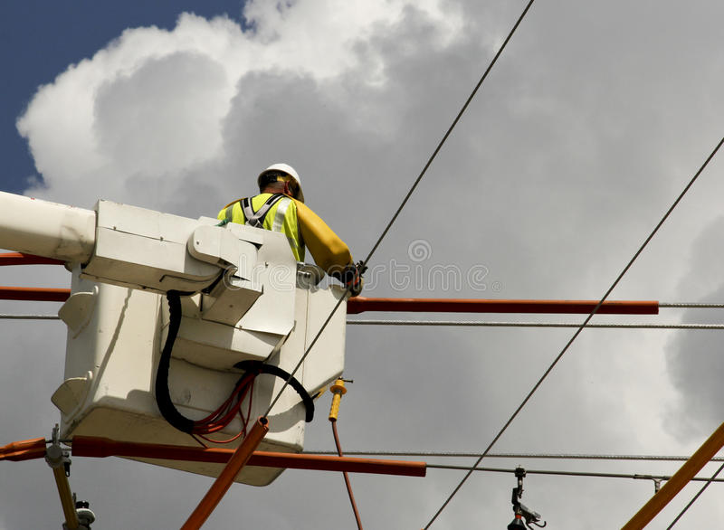 Lineman in a bucket. Hooking up high voltage wires stock photography