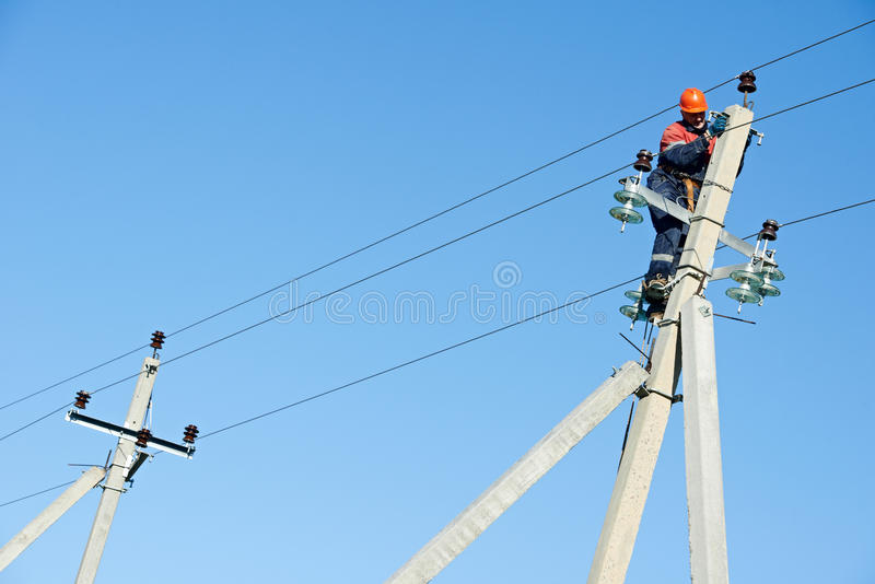 Lineman do eletricista do poder no trabalho no polo fotos de stock royalty free