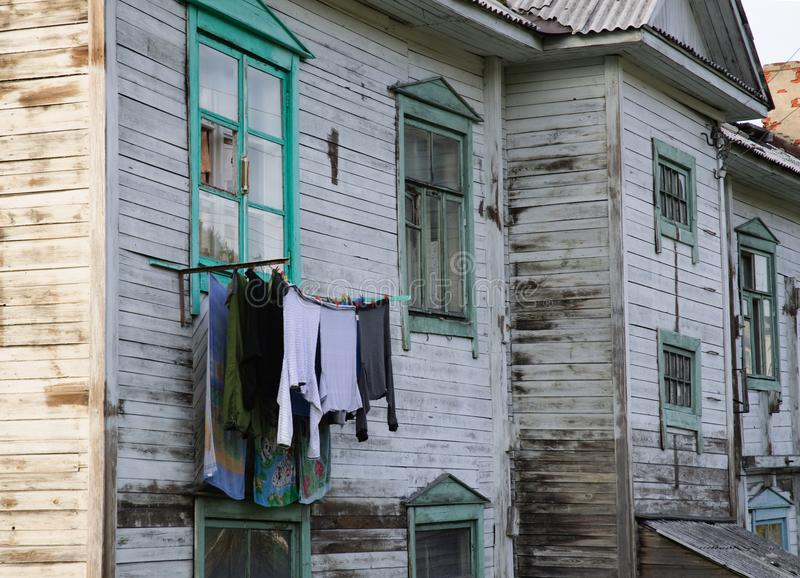 The linen is hung to dry out the window of an old wooden barrack royalty free stock images