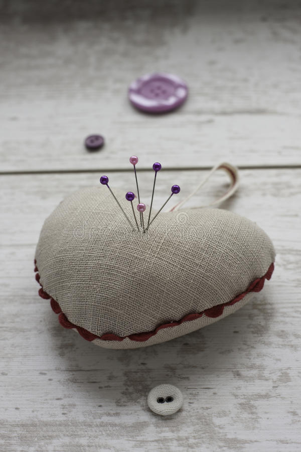 Linen pin-cushion with colored pins. Linen heart shape pin-cushion with colored pins and buttons on the table stock images