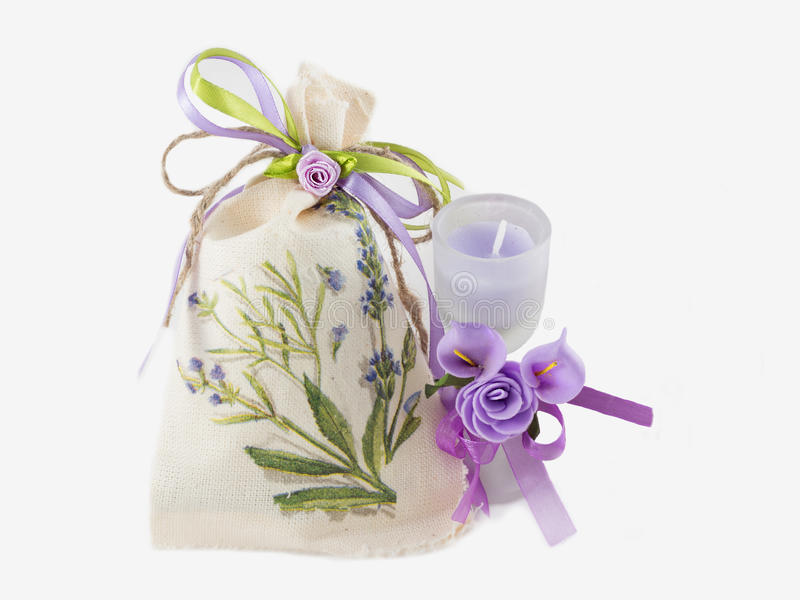 Linen sack and aroma candle in glass decorated. Handmade Linen sack and aroma candle in glass decorated with artificial flowers on white background stock images