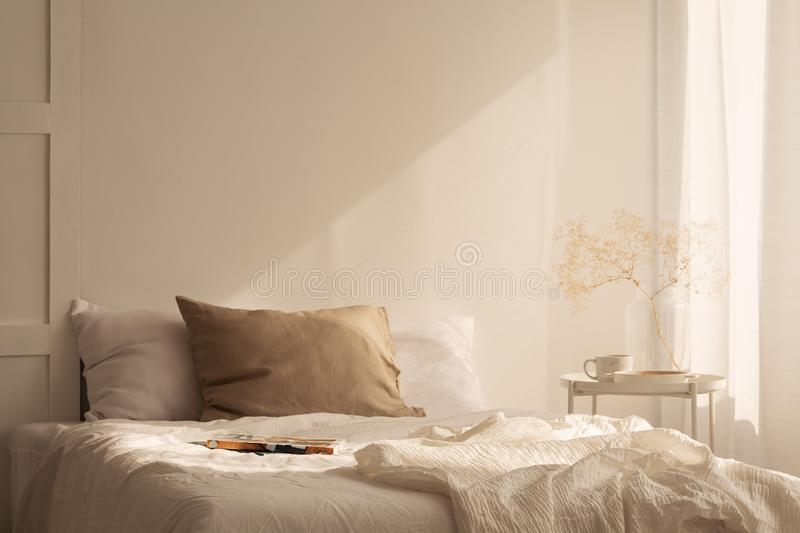 Linen sheets ion king size bed in minimal bedroom with empty wall. Linen sheets ion king size bed in minimal bedroom interior of stylish house, real photo with stock images